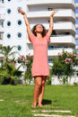 Young woman raised her hands enjoying the sun near building Royalty Free Stock Photography