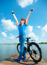 Young woman raised her hands up in joy happy standing near bicycle outdoor shoot Stock Photos
