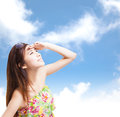Young woman raising hand to cover sunlight with blue sky background Royalty Free Stock Image