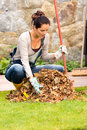 Young woman raking dry leaves autumn backyard pile housework fall Stock Photography