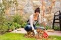 Young woman raking leaves autumn pile veranda Royalty Free Stock Photo