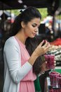Young woman with raspberries buying at the market Royalty Free Stock Image