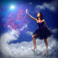 Young woman reaching for a glowing star around abstract background Stock Photography