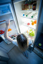 Young woman reaching for refrigerator top shelf at night Royalty Free Stock Photo