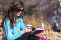 Young woman reading a book in an autumn park beautiful with cup of coffee the hand Stock Photos
