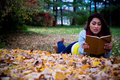 Young woman reading a book lying down on autumn leaves in the fa Royalty Free Stock Photo