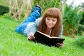 image photo : Young woman reading a book lying on the grass