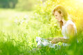 Young woman reading a book on nature, sitting on the grass in the park. Royalty Free Stock Photo
