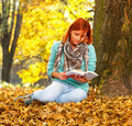 Young woman reading a book in nature sitting on the leaves the park on autumn day Royalty Free Stock Photo