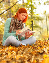 Young woman reading a book in nature sitting on the leaves the park on autumn day Stock Photography
