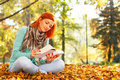 Young woman reading a book in nature sitting on the leaves the park on autumn day Stock Images