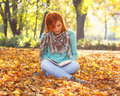 Young woman reading a book in nature sitting on the leaves the park on autumn day Royalty Free Stock Image