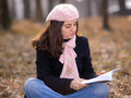 Young woman reading a book outdoors Stock Photos