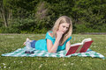 Young woman reading book in park laying on blanket Stock Images