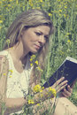 Young woman reading a book on the rape meadow Royalty Free Stock Photo