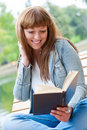 Young woman reading a book sitting on the bench Royalty Free Stock Photos