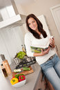 Young woman reading cookbook in the kitchen Royalty Free Stock Photography
