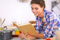 Young woman reading cookbook in the kitchen looking for recipe Stock Photography