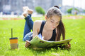 Young woman reading magazine lying on grass Royalty Free Stock Photo