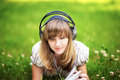 Young woman reading on nature smiling and listening to the music with big headphones Stock Images