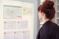 Young woman reading notices on a board with her red hair in bun standing bulletin indoors profile view from behind Royalty Free Stock Photos