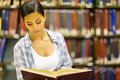 Young woman reading pretty a book in library Royalty Free Stock Photo