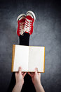 Young woman reading pulp fiction book with her feet raised in the air blank pages as copy space Royalty Free Stock Images