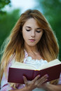 Young woman reading red book Stock Photos