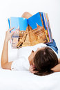 Young woman reading travel magazine on the sofa or in bed isolated on white background i am the author of the photos in the Stock Photo