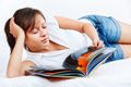 Young woman reading travel magazine on the sofa or in bed isolated on white background inspector note i am the author of the Stock Photo