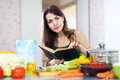 Young  woman reads cookbook for recipe Stock Photos