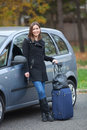 Young woman ready to travel beautiful standing by the car with luggage Stock Photography