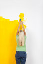 Young woman rear view putting a yellow paint on the wall Stock Image