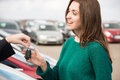 Young woman receiving key in front of cars outside car dealership Royalty Free Stock Photo