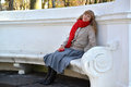 The young woman with red apple in a hand sits on a bench in the park Royalty Free Stock Photo