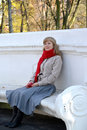 The young woman with red apple sits on a bench in the autumn pakr Royalty Free Stock Photo