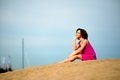 Young woman in a red dress ans curly hair sit on the sand Royalty Free Stock Photo