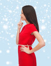 Young woman in red dress choosing advertisement concept attractive with finger on her lips Royalty Free Stock Images
