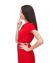 Young woman in red dress choosing advertisement concept attractive with finger on her lips Royalty Free Stock Photos