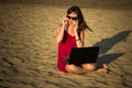 Young woman in red dress with computer and smartphone on the beach. Freelance and downshifting concept.