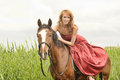 Young woman in a red dress on a horse Stock Photography