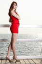Young woman in red dress on the pier full length morning summer holiday Stock Image
