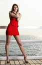 Young woman in red dress on the pier full length morning summer holiday Royalty Free Stock Photos