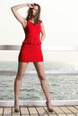 Young woman in red dress on the pier full length morning summer holiday Royalty Free Stock Photo
