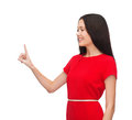 Young woman in red dress pointing her finger advertisement concept attractive Royalty Free Stock Photography