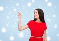 Young woman in red dress pointing her finger advertisement concept attractive Stock Photo