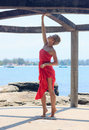 Young woman in red dress standing on tiptoe inside round alcove on sunny day with seaview at background view Stock Photos