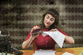 Young woman with red dress stapling papers in office Stock Photos