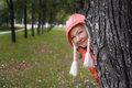 Young woman in red jacket looks out of the autumn park tree Stock Photography