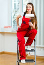 Young woman red overall renovating her apartment relocated to her new home Royalty Free Stock Image